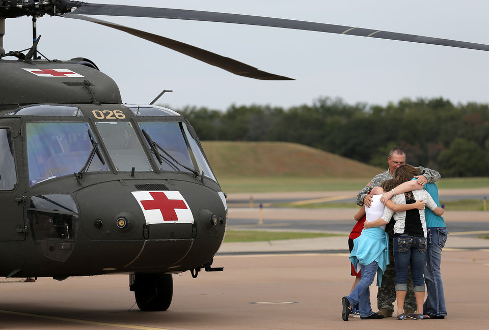 Staff Sgt. David Tillman says goodbye to his son, Patrick, daughters, Meagan, and Abby and wife Tiffany following a Oklahoma Aviation Command mobilization ceremony for Detachment 1, Company C, 2-149th General Support Aviation Battalion at the Army Aviation Support Facility in Lexington, Okla., Sunday, Sept. 16, 2012. The soldiers will receive additional training at Fort Hood before being deployed to Afghanistan. Photo by Sarah Phipps, The Oklahoman