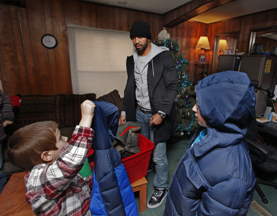 Photo - CHILD / CHILDREN / KIDS / DANE SHELBY / CHRISTMAS / HOLIDAY / GIFTS: Baseball superstar Matt Kemp gives coats to Dane, 7,  and Randall Shelby, 11, as he delivers presents to a trailer community on Thursday, Dec. 22, 2011, in Midwest City, Okla.   Photo by Steve Sisney, The Oklahoman