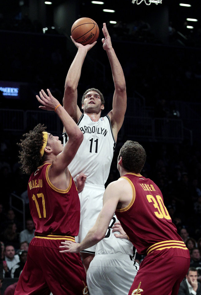 Brooklyn Nets' Brook Lopez (11) shoots over Cleveland Cavaliers' Anderson Varejao (17) and Jon Leuer (30) during the first half of an NBA basketball game, Tuesday, Nov. 13, 2012, in New York. (AP Photo/Frank Franklin II)