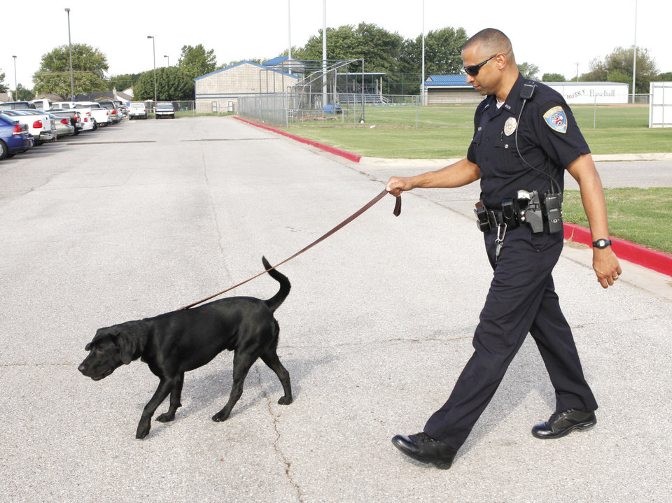 Photo - Edmond police officer Dack Pearson walks Justice through the parking lot at Edmond North High School in 2010.  PAUL HELLSTERN