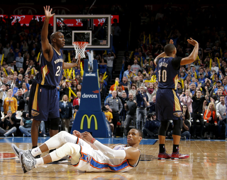 Photo - Oklahoma City's Russell Westbrook (0) looks up as New Orleans' Quincy Pondexter (20) and Eric Gordon (10) protest a called foul during the last seconds of an NBA game between the Oklahoma City Thunder and the New Orleans Pelicans at Chesapeake Energy Arena on Friday, Feb. 6, 2015. Photo by Bryan Terry, The Oklahoman