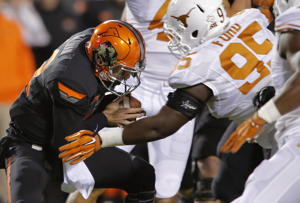 Photo - Oklahoma State's Daxx Garman (12) is sacked by Texas' Poona Ford (95) during the college football game between the Oklahoma State University Cowboys (OSU) the University of Texas Longhorns (UT) at Boone Pickens Staduim in Stillwater, Okla. on Saturday, Nov. 15, 2014.  Photo by Chris Landsberger, The Oklahoman