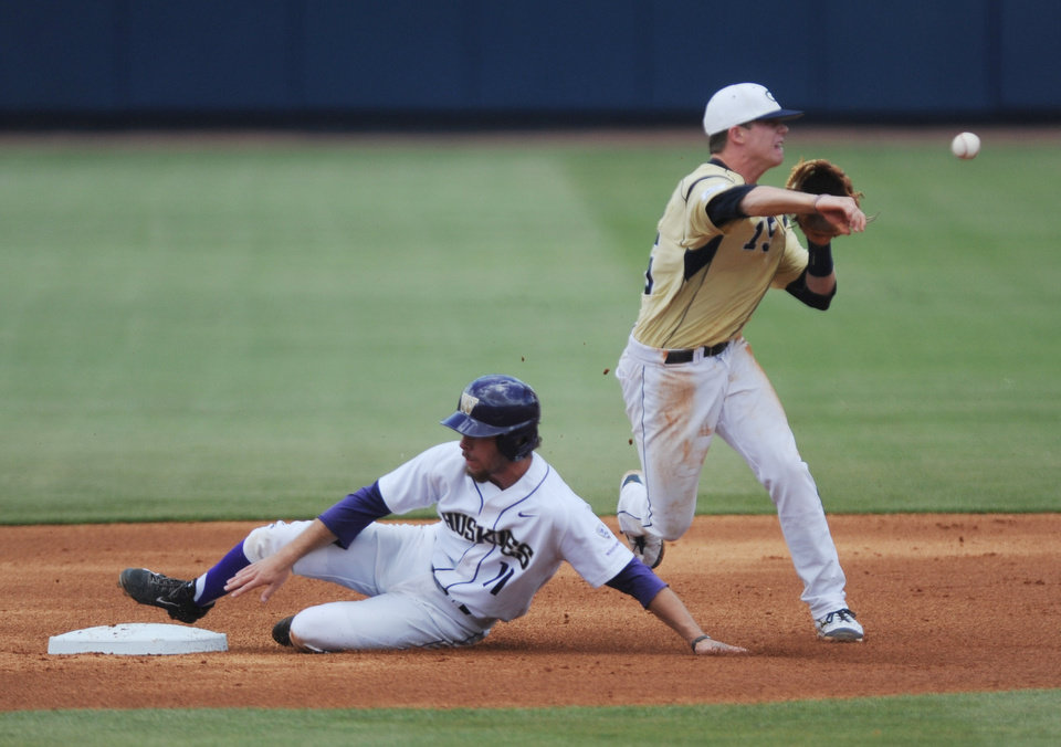 Photo - Georgia Tech's Connor Justus, right, forces out Washington's Austin Rei, left, and throws to first for a double play at the NCAA Oxford Regional at Oxford-University Stadium on Saturday, May 31, 2014. (AP Photo/The Oxford Eagle, Bruce Newman)
