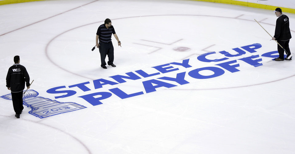 Photo - Workers position a Stanley Cup Playoffs logo onto the ice at TD Garden in Boston, following an NHL hockey game between the Ottawa Senators and the Boston Bruins on Sunday, April 28, 2013. The Senators won 4-2. (AP Photo/Steven Senne)
