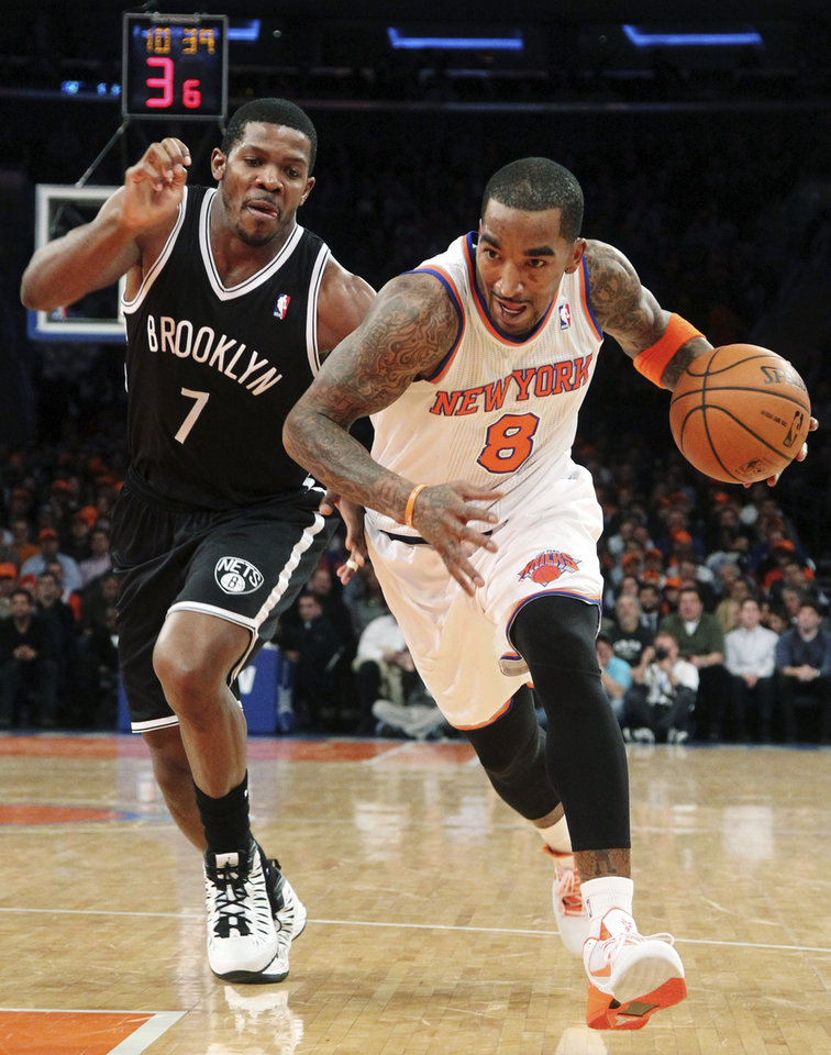 Photo - New York Knicks' J.R. Smith (8) drives past Brooklyn Nets' Joe Johnson during the first half of NBA basketball game, Wednesday, Dec. 19, 2012, at Madison Square Garden in New York. The Knicks won 100-86. (AP Photo/Mary Altaffer)