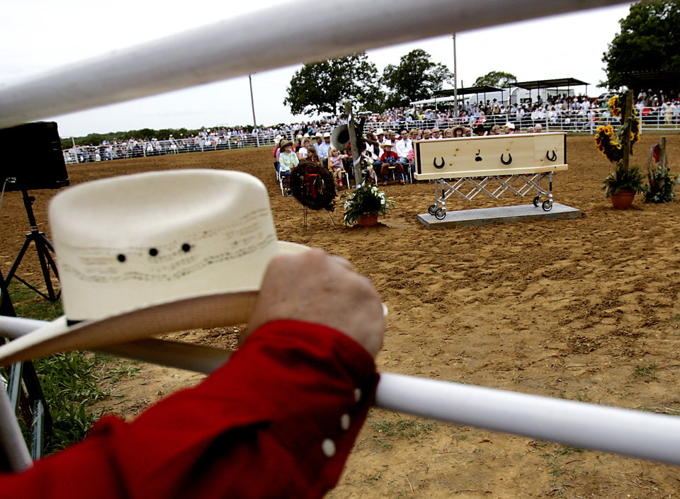 Photo - An onlooker rests his hat on the railing as Jim Shoulder's pine-box casket sits inside the Jim Shoulders Living Legends Rodeo Arena in Henryetta, Okla., during funeral services for Jim Shoulders on Sunday,  June 24, 2007. By John Clanton, The Oklahoman