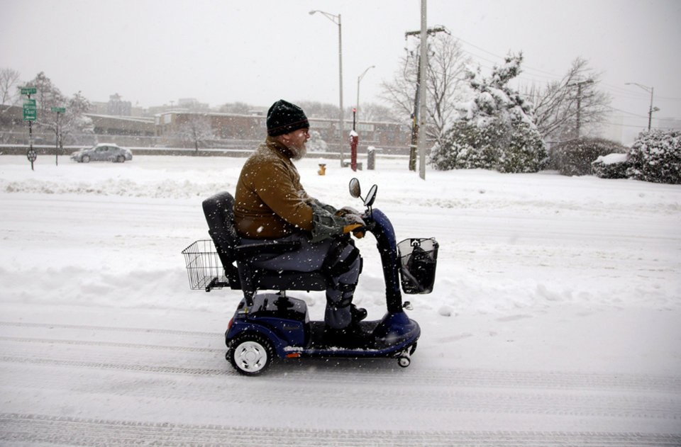 Photo - A man drives his scooter in the left lane of Granite Street during a snowstorm in Quincy, Mass., Wednesday, Feb. 5, 2014. The storm is expected to drop a foot or more of snow on some areas of the Massachusetts Wednesday making driving treacherous.(AP Photo/Stephan Savoia)