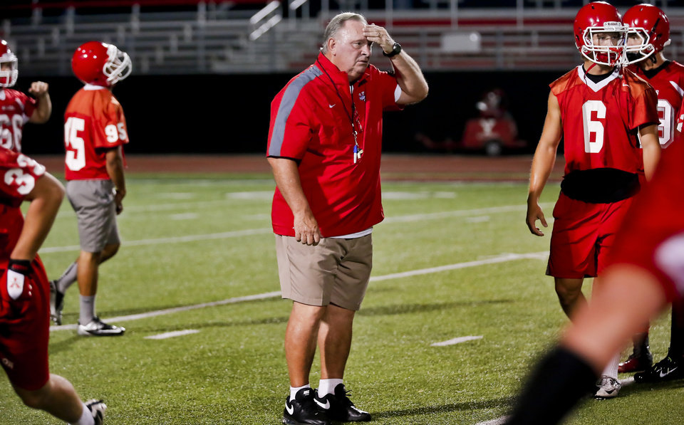 Photo - Former Oklahoma State University football assistant coach Bill Young works with his Yukon High School football team as he takes his first stint as a head coach on the first day of team practice in Yukon, Okla. on Monday, Aug. 11, 2014. Photo by Chris Landsberger, The Oklahoman