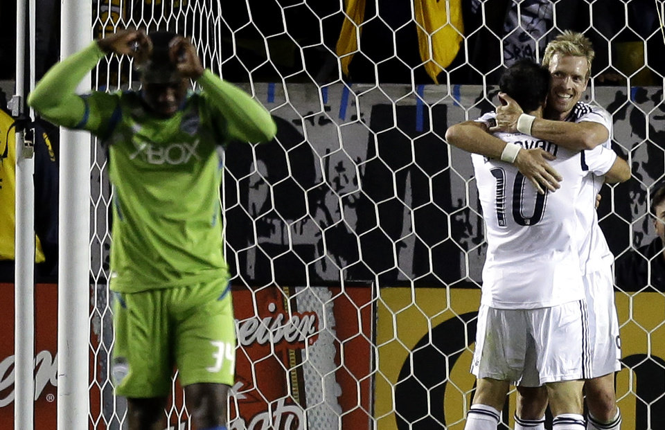 Photo -   Los Angeles Galaxy's Chad Barrett, right, and Landon Donovan celebrate Robbie Keane's goal as Seattle Sounders' Jhon Kennedy Hurtado walks away during the second half of an MLS Western Conference finals soccer game in Carson, Calif., Sunday, Nov. 11, 2012. The Galaxy won 3-0. (AP Photo/Chris Carlson)