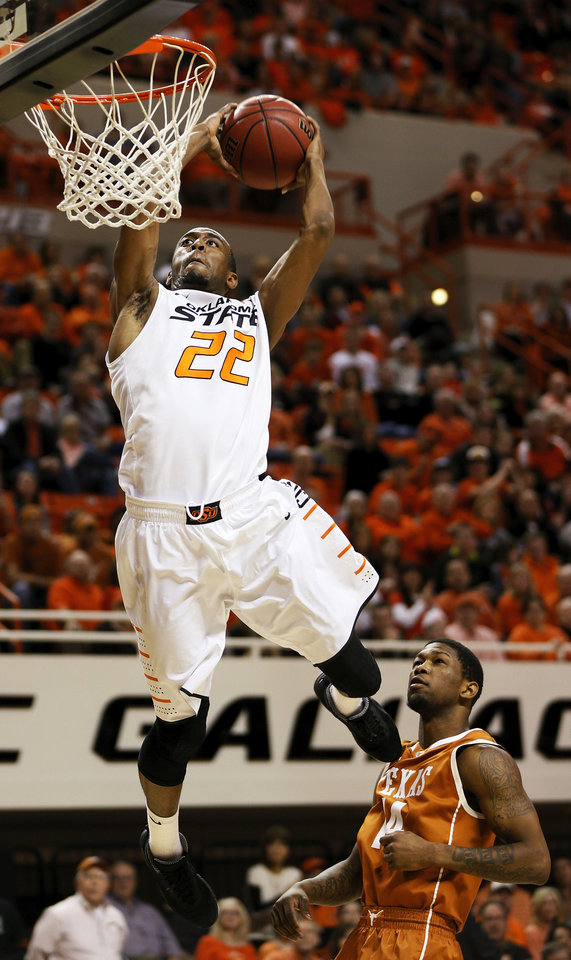 Photo - Oklahoma State's Markel Brown (22) dunks the ball in front of Texas' Julien Lewis (14) during a men's college basketball game between Oklahoma State University (OSU) and the University of Texas at Gallagher-Iba Arena in Stillwater, Okla., Saturday, March 2, 2013. Photo by Nate Billings, The Oklahoman