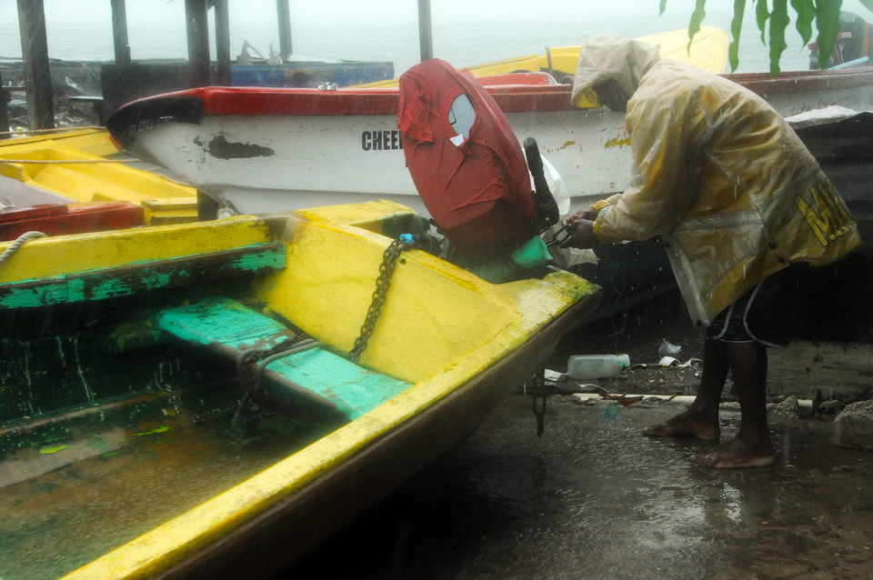 Photo -   Fisherman Hubert Dowie works to secure his boat before the arrival of Hurricane Sandy in Port Royal, Jamaica, Wednesday, Oct. 24, 2012. Hurricane Sandy pounded Jamaica with heavy rain as it headed for landfall near the country's most populous city on a track that would carry it across the Caribbean island to Cuba, and a possible threat to Florida. (AP Photo/Collin Reid)