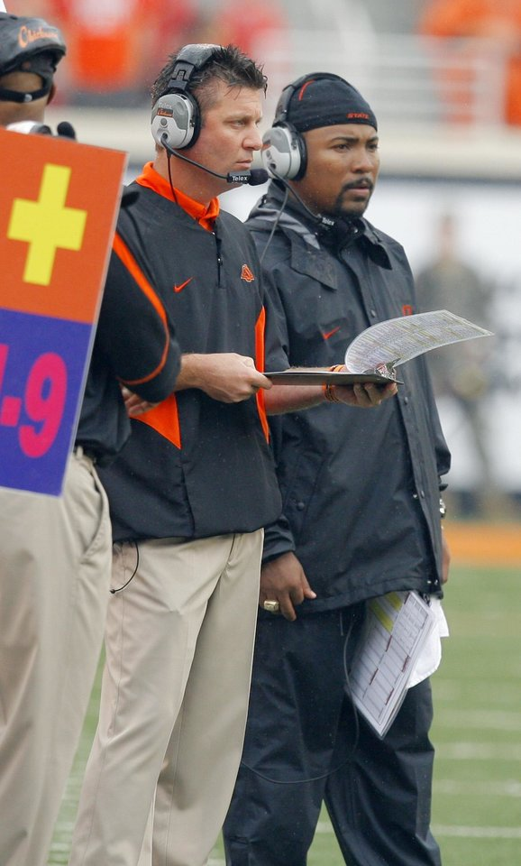 Photo - Head coach Mike Gundy looks at his plays as Trooper Taylor looks on the field at the Oklahoma State University (OSU) college football game against Missouri State University (MSU) Saturday Sept. 13, 2008 at Boone Pickens Stadium in Stillwater, Okla. BY MATT STRASEN, THE OKLAHOMAN. ORG XMIT: KOD