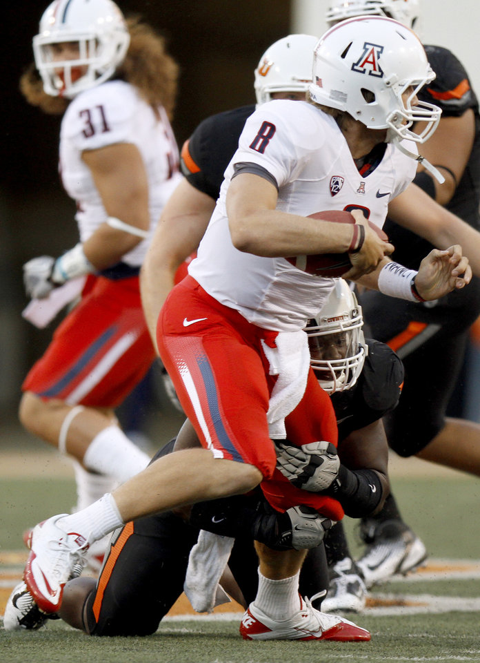 Oklahoma State\'s Nigel Nicholas brings down Arizona quarterback Nick Foles for a sack during their game Thursday. OSU got pressure on Foles for most of the first half, but could only bring him down this one time. PHOTO BY BRYAN TERRY, The Oklahoman
