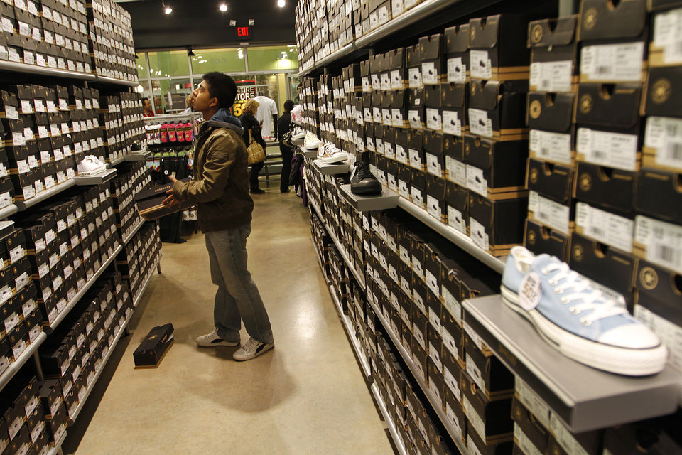 Photo - Eddy Caballeros, of Oklahoma City, looks at shoes at the Converse outlet during Black Friday at The Outlet Shoppes at Oklahoma City, Thursday, Nov. 24, 2011.  Photo by Garett Fisbeck, For The Oklahoman