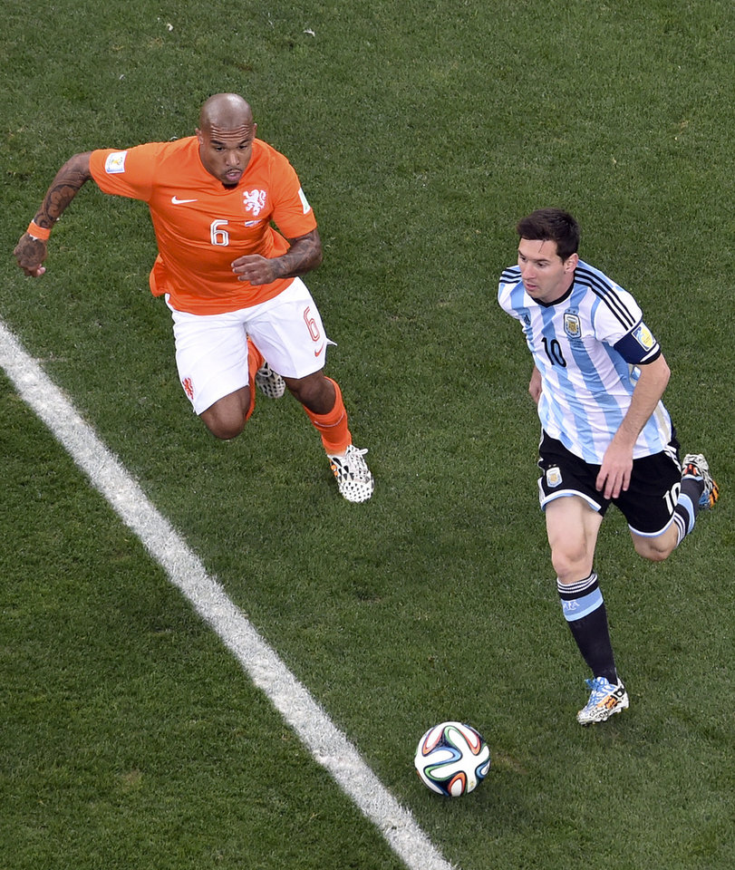 Photo - Argentina's Lionel Messi, right, is chased by Netherlands' Nigel de Jong (6) during the World Cup semifinal soccer match between the Netherlands and Argentina at the Itaquerao Stadium in Sao Paulo, Brazil, Wednesday, July 9, 2014. (AP Photo/Francois Xavier Marit, Pool)