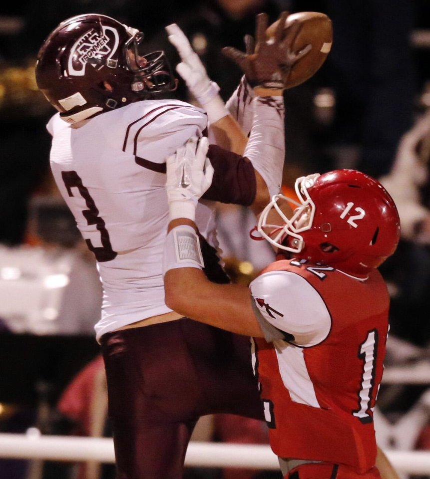 Photo - Nowata's Bryce Bell catches a pass over defender Glenn Stowe as the Nowata Ironmen play the Washington Warriors in high school football on Friday, Nov. 28, 2014 in Washington, Okla. Photo by Steve Sisney, The Oklahoman