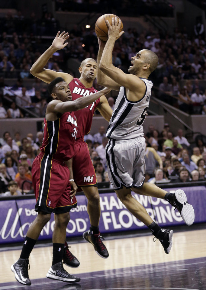 Photo - San Antonio Spurs' Tony Parker (9), of France, drives to the basket as Miami Heat's Norris Cole (30) and Shane Battier, center, defend him during the first half of an NBA basketball game, Sunday, March 31, 2013, in San Antonio. (AP Photo/Eric Gay)