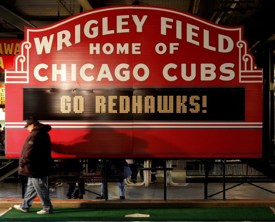 Photo - A man drags his hand across the replica of the Wrigley field marquee on the concourse during the minor league baseball game between the Oklahom City RedHawks and the New Orleans Zephyrs at AT&T Bricktown Ballpark Friday, May 1, 2009. Tonight was Taste of the Big Leagues night featuring Wrigley Field in Chicago. Photo by Doug Hoke, The Oklahoman ORG XMIT: KOD