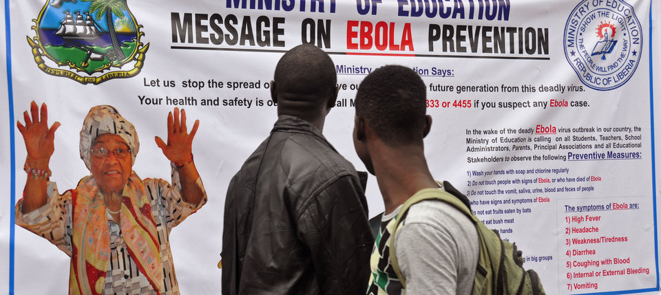 Photo - The image of Liberia President Ellen Johnson Sirleaf, left, appears on a public information banner warning people about the Ebola virus in the city of Monrovia, Liberia, Friday, Aug. 8, 2014. The World Health Organization urged nations worldwide to donate money and resources to stop the spread of Ebola as it declared the outbreak in West Africa to be an international public health emergency. (AP Photo/Abbas Dulleh)