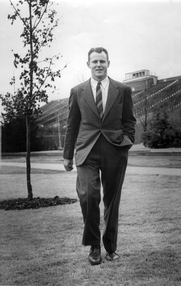 Photo - OU head coach Bud Wilkinson strolls across campus in this 1947 photo with Memorial Stadium in the background. (Oklahoma Archives)