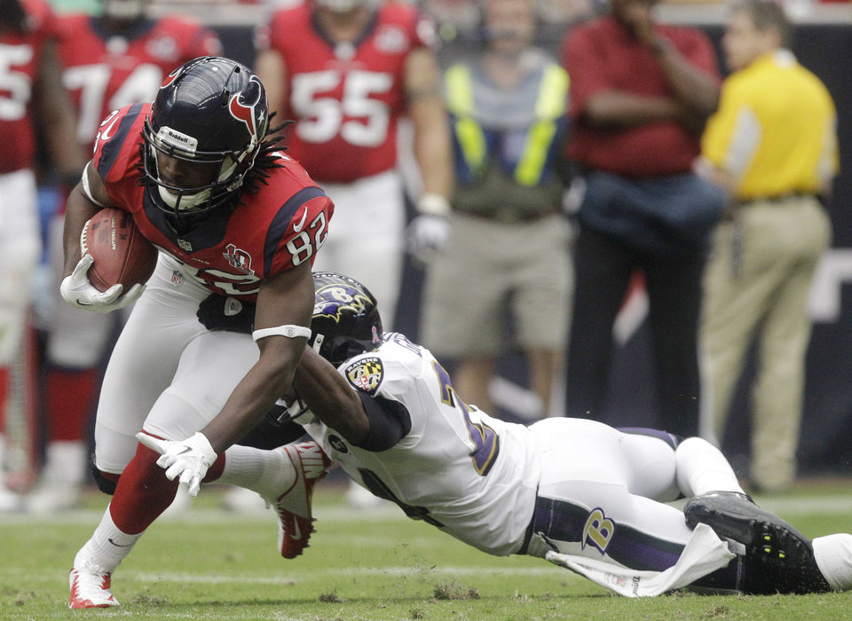 Photo -   Baltimore Ravens defensive back Corey Graham (4) tackles Houston Texans wide receiver Keshawn Martin (82) during the second quarter of an NFL football game Sunday, Oct. 21, 2012, in Houston. (AP Photo/Patric Schneider)