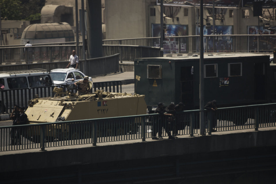 Photo - An Egyptian army armored vehicle and a riot police truck are seen on a bridge over the Nile river at Zamalek District in Cairo, Egypt, Saturday, Aug. 17, 2013. Authorities say police in Cairo are negotiating with people barricaded in a mosque and promising them safe passage if they leave. Muslim Brotherhood supporters of Egypt's ousted Islamist president Mohamed Morsi are vowing to defy a state of emergency with new protests today, adding to the tension. (AP Photo/Manu Brabo)