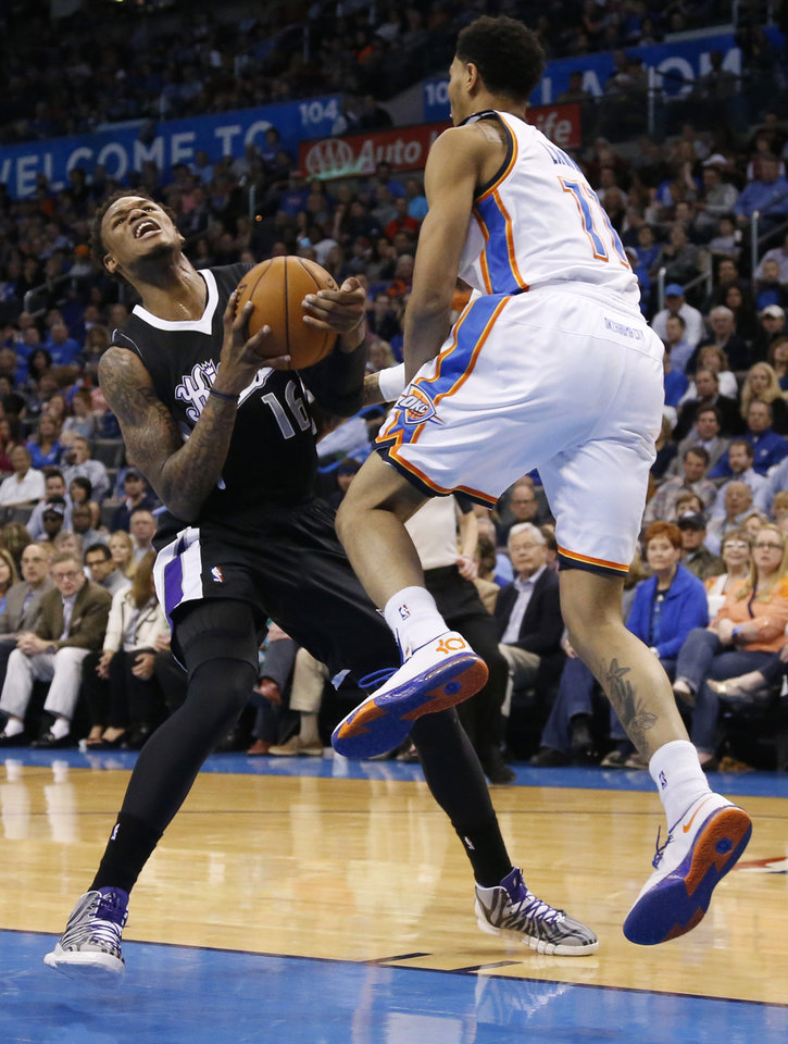 Photo - Sacramento Kings guard Ben McLemore (16) is fouled by Oklahoma City Thunder guard Jeremy Lamb (11) during the first quarter of an NBA basketball game in Oklahoma City, Friday, March 28, 2014. (AP Photo/Sue Ogrocki)