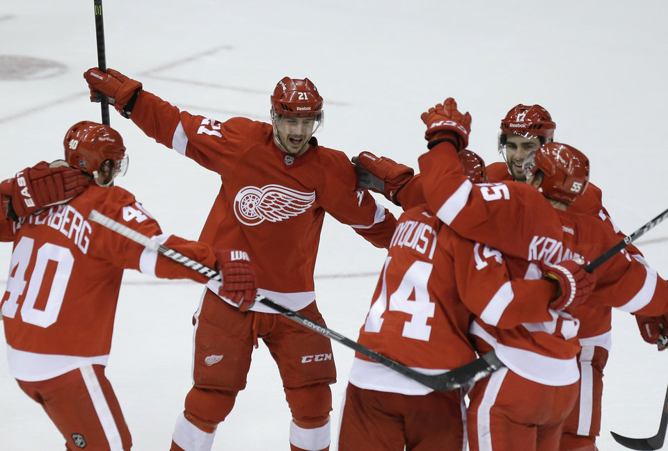 Photo - Detroit Red Wings left wing Tomas Tatar (21), of the Czech Republic, rushes in to celebrate the goal by defenseman Niklas Kronwall (55), of Sweden, during the third period of an NHL hockey game against the Los Angeles Kings in Detroit, Saturday, Jan. 18, 2014. (AP Photo/Carlos Osorio)