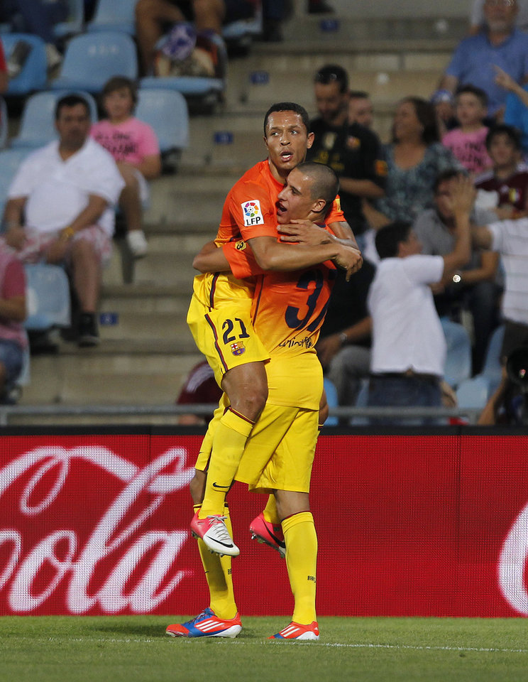 Photo -   FC Barcelona's Adriano Correia from Brazil, top, celebrates his goal with Tello during a Spanish La Liga soccer match against Getafe at the Coliseum Alfonso Perez stadium in Getafe, near Madrid, Spain, Saturday, Sept. 15, 2012. (AP Photo/Andres Kudacki)