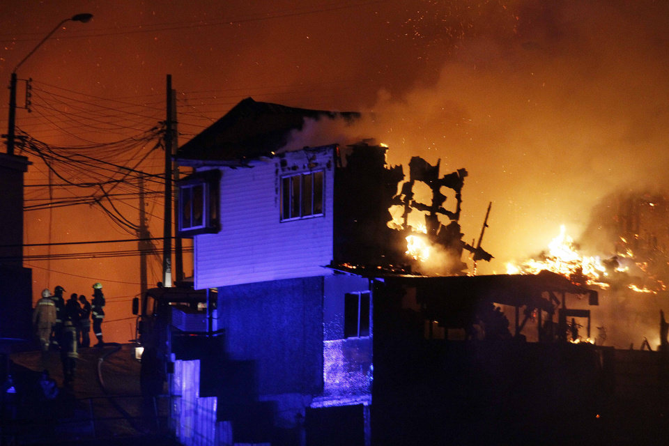 Photo - A group of firefighters stand next to burning homes as a forest fire rages towards urban areas in the city of Valparaiso, Chile, Sunday April 13, 2014. Authorities say the first fire has destroyed at least 150 homes and is forcing evacuations.( AP Photo/ Luis Hidalgo