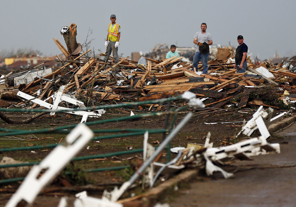 Men look through debris north of SW 149th and east of Western after a tornado struck south Oklahoma City and Moore, Okla., Monday, May 20, 2013. Photo by Nate Billings, The Oklahoman