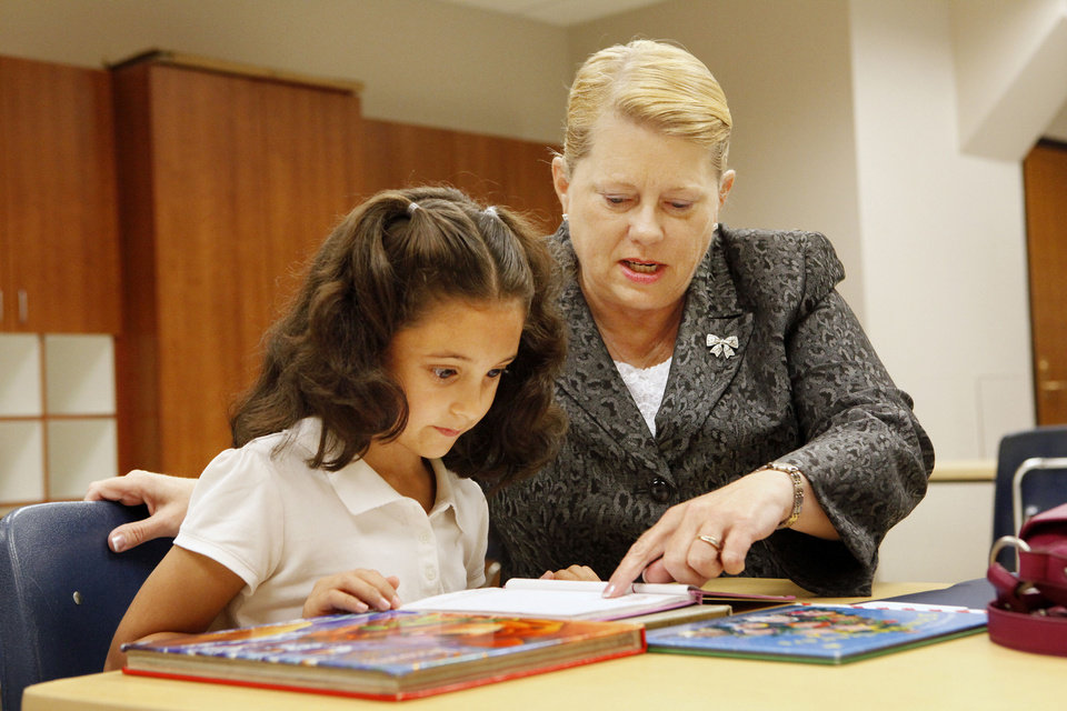 Photo - Laura Johnson, assistant Oklahoma City manager, works with first grader Vanessa Esparza, 6, on Thursday at Heronville Elementary School in Oklahoma City. A reading buddies program with students and city employees is one of the programs with roots in a task force of city council members and school officials.  PAUL B. SOUTHERLAND - The Oklahoman