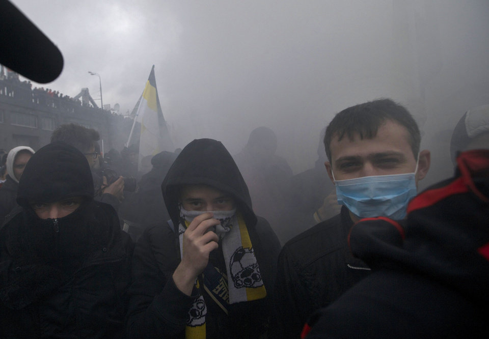 "Ultra nationalist demonstrators and activists cover their faces after a smoke bomb was set off, as they march to mark National Unity Day, on the outskirts of Moscow, on Sunday, Nov. 4, 2012. Chanting ""Russia for Russians"" and ""Migrants today, occupiers tomorrow,"" about 6,000 people, mostly young men, marched through a working-class neighborhood on the outskirts of the capital, while police stood shoulder to shoulder along streets blocked to traffic. (AP Photo/Ivan Sekretarev)"