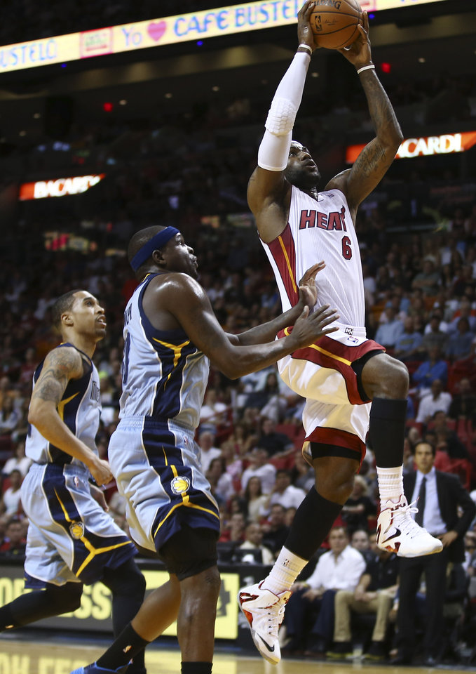 Photo - Miami Heat's LeBron's scores after getting past Memphis Grizzlies' Courtney Lee, left, and Zach Randolph during the first half of an NBA basketball game in Miami, Friday, March 21, 2014. (AP Photo/J Pat Carter)