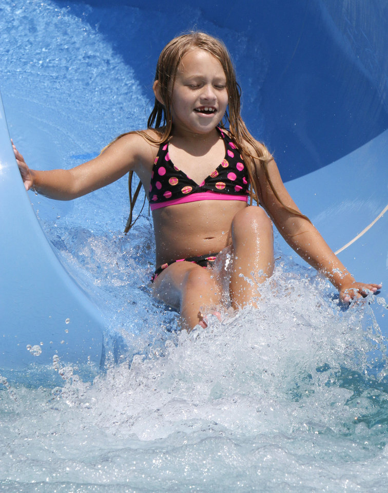 Photo -  Tarin Bondurant, 8, hits the water at the bottom of one of the water slides at Pelican Bay Aquatic Center. Photo by Paul Hellstern, The Oklahoman   PAUL HELLSTERN -