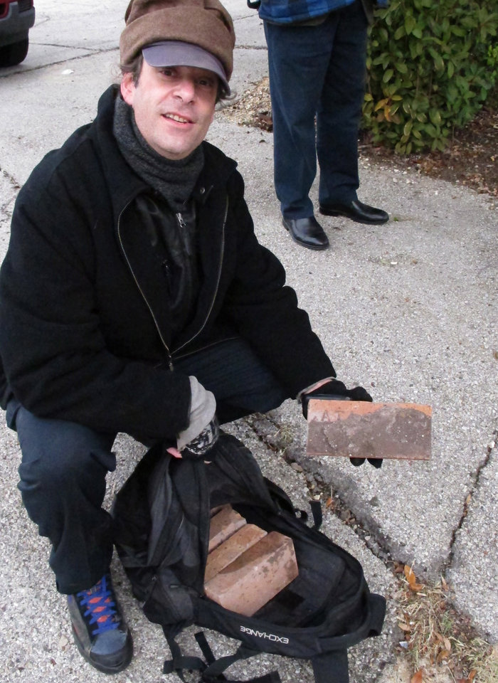 Tom Sclar, 46, a Dallas musician and longtime enthusiast of John F. Kennedy assassination history, holds bricks taken from a two-story apartment complex where JFK assassin Lee Harvey Oswald once lived, on Monday, January 14, 2013, in Dallas, Texas. The rundown two-story building in southwest Dallas was demolished Monday by the city. (AP Photo/Nomaan Merchant)