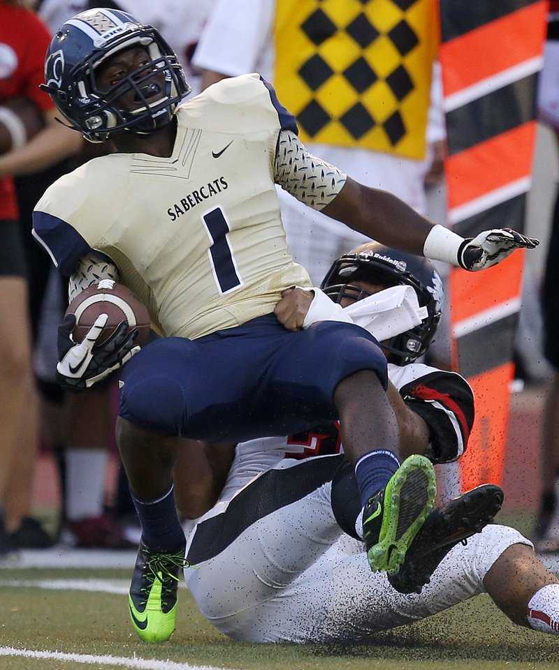 Southmoore's Nick Scott is brought down by Westmoore's Cassius Hill during their high school football game in Moore, Okla., Friday, Sept. 13, 2013. Photo by Bryan Terry, The Oklahoman