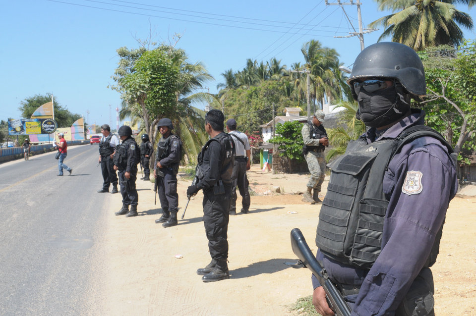 Photo - State police stand at a roadblock due to stepped up security after masked armed men broke into a beach home, raping six Spanish tourists who had rented the house in Acapulco, Mexico, Tuesday Feb. 5, 2013. According to the mayor of Acapulco, five masked men burst into a house the Spaniards had rented on the outskirts of Acapulco, in a low-key area near the beach, and held a group of six Spanish men and one Mexican woman at gunpoint, while they raped the Spanish women before dawn on Monday. (AP Photo/Bernandino Hernandez)