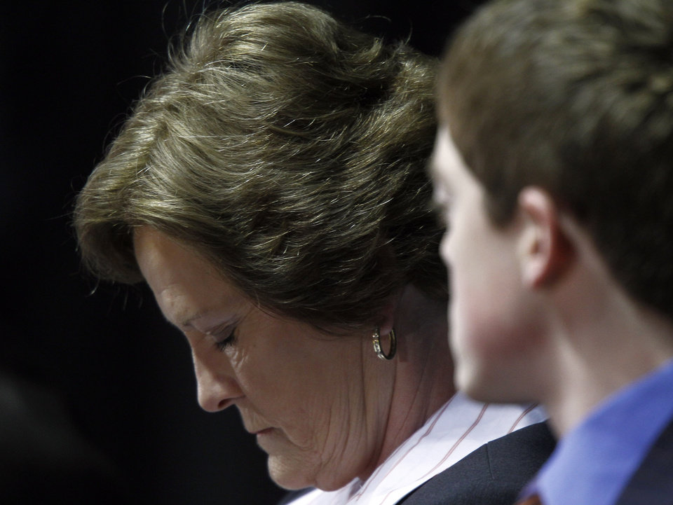 "Former Tennessee women's college basketball coach Pat Summitt bows her head as her son Tyler Summitt looks on as she appears at a news conference Thursday, April 19, 2012, in Knoxville, Tenn. Summitt said it's been a ""great ride"" and it is the right time for her to step down after coaching the Tennessee Lady Vols for nearly four decades. (AP Photo/Wade Payne)"