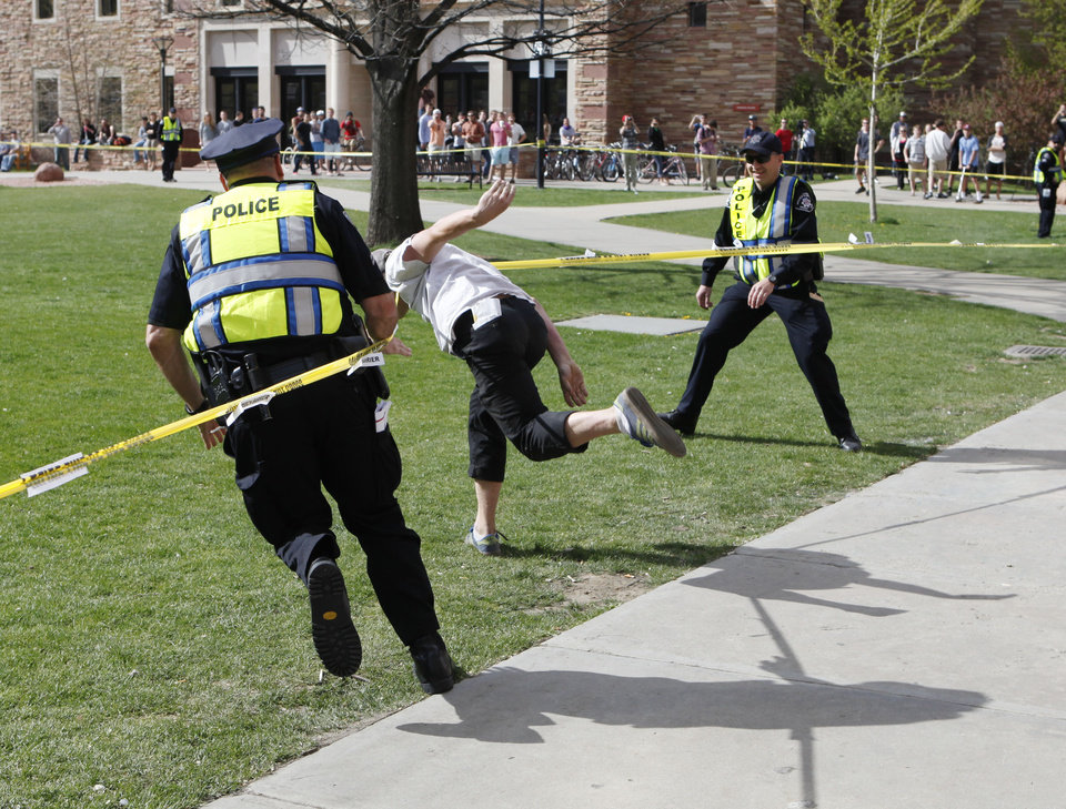 Photo -   Police try to stop a student as he runs through the police barrier on the Norlin Quad at the University of Colorado in Boulder, Colo., on Friday, April 20, 2012, at 4:20pm. He was run down by police and arrested after crossing the barrier. Police blocked off the quad to prevent a 420 marijuana smoke out. (AP Photo/Ed Andrieski)