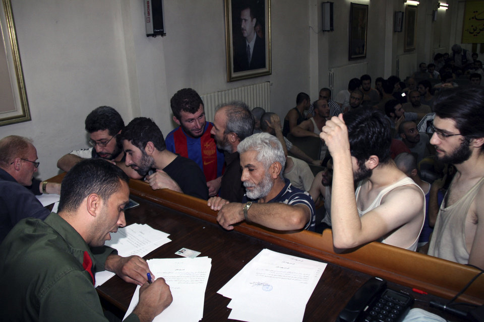 Photo -   Syrian prisoners sign their papers of release at the Damascus Police Command headquarters in Damascus, Syria, Saturday, Sept. 1, 2012. Syria's official state news agency, SANA reported Saturday that 225 detainees, who took part in anti-government protests, were released. The amnesty by authorities is the second in a week as some 378 prisoners from Damascus and the central province of Homs, were freed on Monday. Rights activists say tens of thousands of Syrians have been detained over the past 18 months. (AP Photo/Bassem Tellawi)