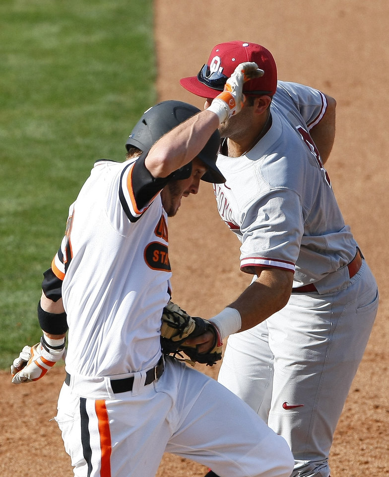 Photo - Oklahoma's first baseman Anthony Hermelyn, back, tags out Oklahoma State's Aaron Cornell, front, in the fourth inning of a first-round game of the Big 12 conference NCAA college baseball tournament in Oklahoma City, Wednesday, May 21, 2014. (AP Photo/Alonzo Adams)
