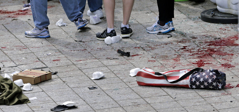 Photo - FILE - In this April 15, 2013, file photo, blood from victims covers the sidewalk on Boylston Street, at the site of an explosion during the 2013 Boston Marathon in Boston. At right foreground is a folding chair with the design of an American flag on the cover. A federal grand jury in Boston returned a 30-count indictment against bombing suspect Dzhokhar Tsarnaev on Thursday, June 27, 2013, on charges including using a weapon of mass destruction and bombing a place of public use, resulting in death. (AP Photo/Charles Krupa, File)