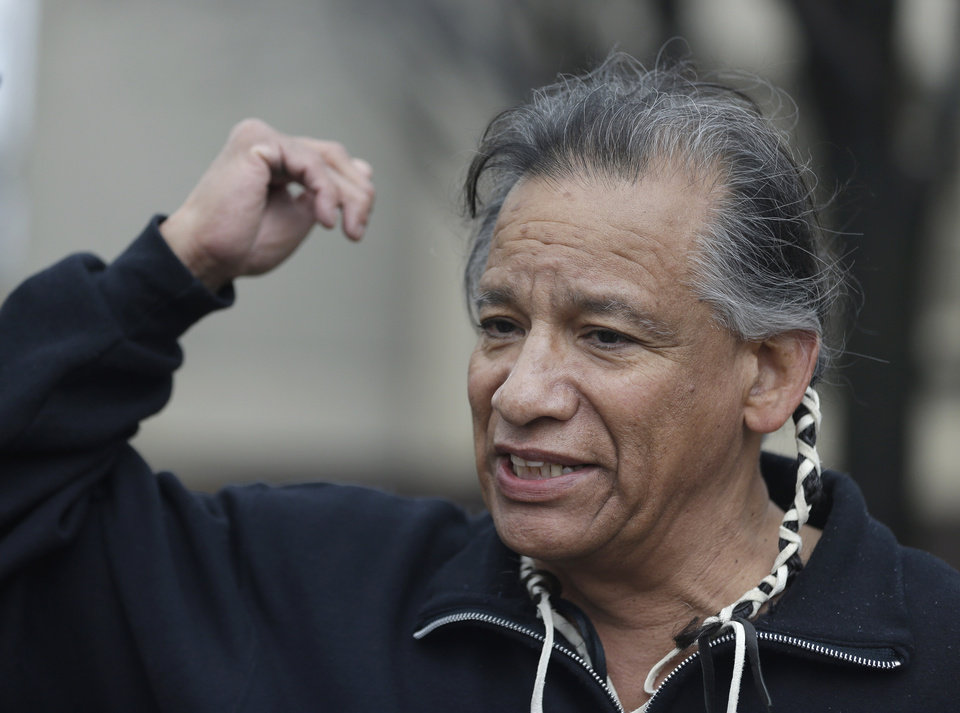Robert Roche, an Apache Native American, says that Native Americans find the use of Chief Wahoo demeaning before a baseball game between the Minnesota Twins and the Cleveland Indians, Friday, April 4, 2014, in Cleveland. (AP Photo/Tony Dejak)