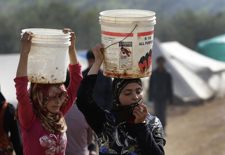Photo - In this Tuesday, Feb. 19, 2013 photo, Syrian refugee girls carry over their heads buckets of water as they walk at Atmeh refugee camp, in the northern Syrian province of Idlib, Syria. This rebel-controlled camp only yards from the border with Turkey houses some 16,000 people displaced by the civil war. But the U.N. and other major aid agencies best equipped to handle such a large-scale relief agency cannot reach them because they are inside Syria. That leaves the job to smaller organizations who can only provide a fraction of the needs. (AP Photo/Hussein Malla)