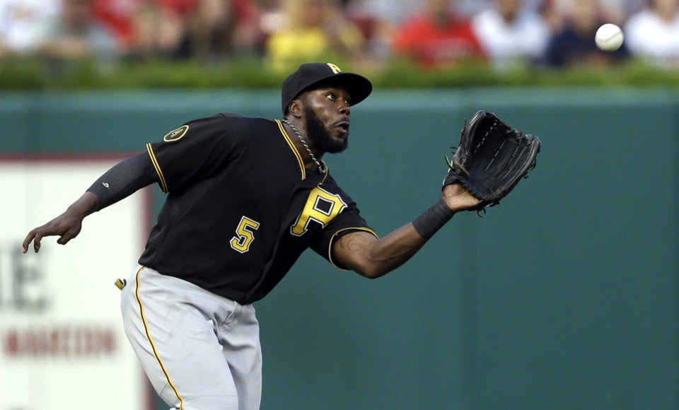 Photo - Pittsburgh Pirates left fielder Josh Harrison  reaches to catch a ball hit by St. Louis Cardinals' Oscar Taveras for an out during the first inning of a baseball game Wednesday, July 9, 2014, in St. Louis. (AP Photo/Jeff Roberson)