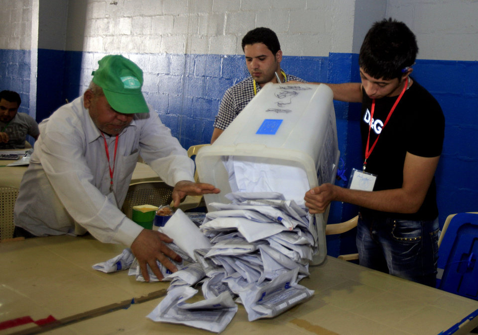 Photo - Iraqi electoral workers empty a ballot box at a counting center in Baghdad, Iraq, Sunday, April 21, 2013. Iraqis have begun counting votes from the first provincial elections since the last U.S. troops withdrew in December 2011. (AP Photo/ Karim Kadim)