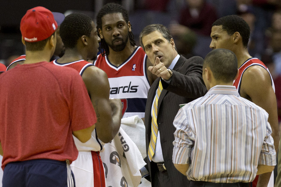 Photo - Washington Wizards head coach Randy Wittman, third from right, speaks with his players during a time out in the fourth quarter of an NBA basketball game against the Orlando Magic at the Verizon Center in Washington, Friday, Dec. 28, 2012. Washington won 105-97. (AP Photo/Jacquelyn Martin)