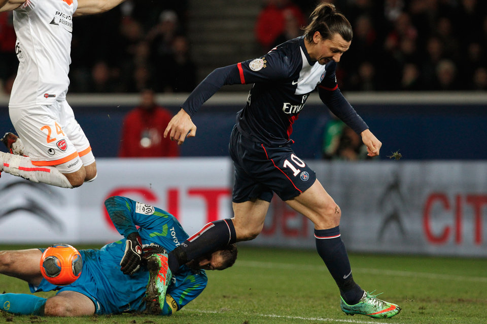 Photo - Paris Saint Germain's Zlatan Ibrahimovici, right, challenges for the ball with Valencienne's Nicolas Penneteau, bottom, during their French League one soccer match, at the Parc des Princes stadium, in Paris, Friday, Feb. 14, 2014. (AP Photo/Thibault Camus)