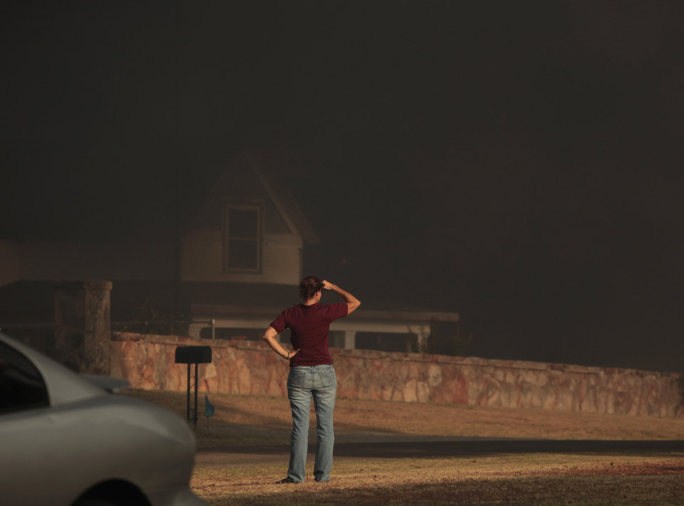 Photo - A resident looks at the smoke building in a large wildfire in Luther, Okla., Friday, Aug. 3, 2012. Photo by Sarah Phipps, The Oklahoman